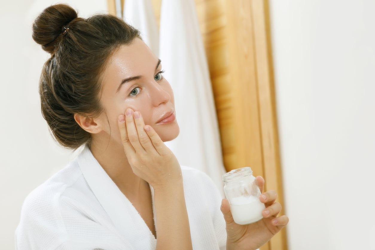 femme salle de bain prendre soin peau miroir peignoir crème visage