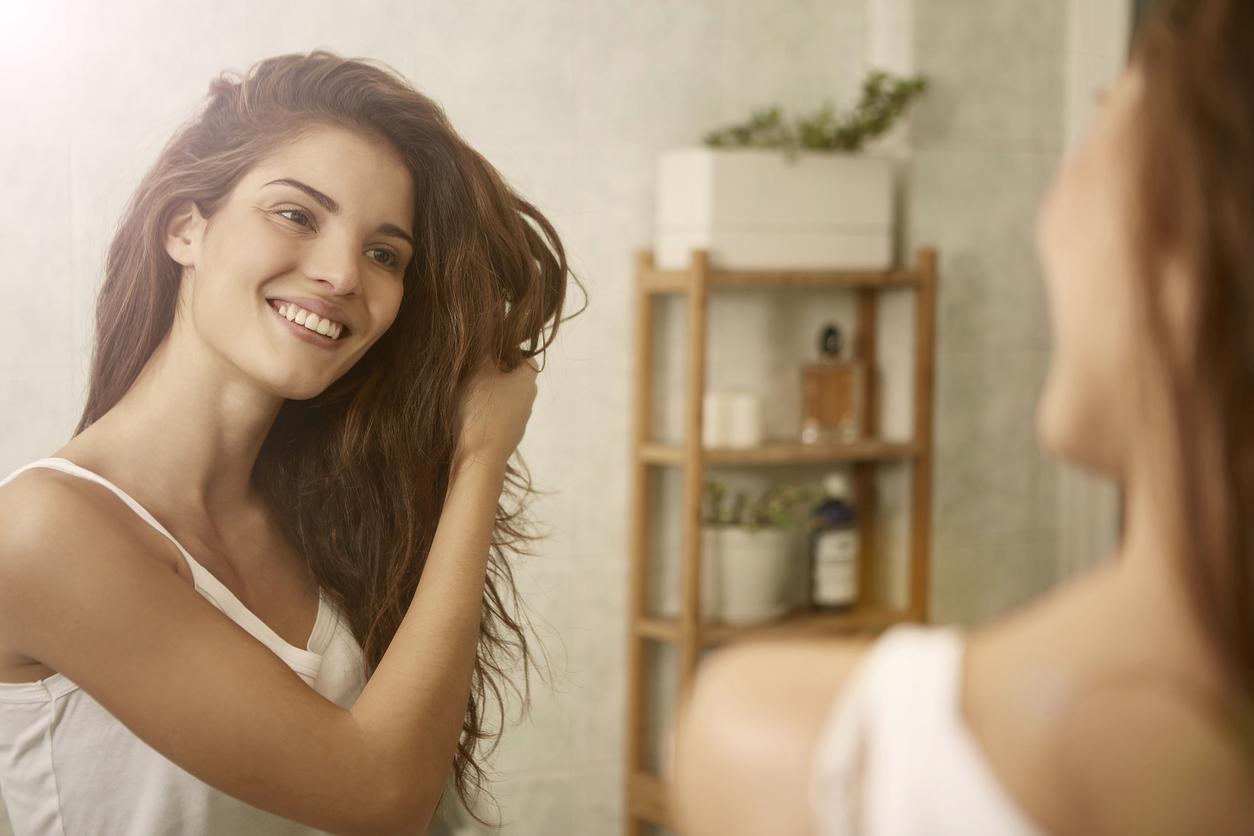 femme brosser cheveux miroir salle de bain