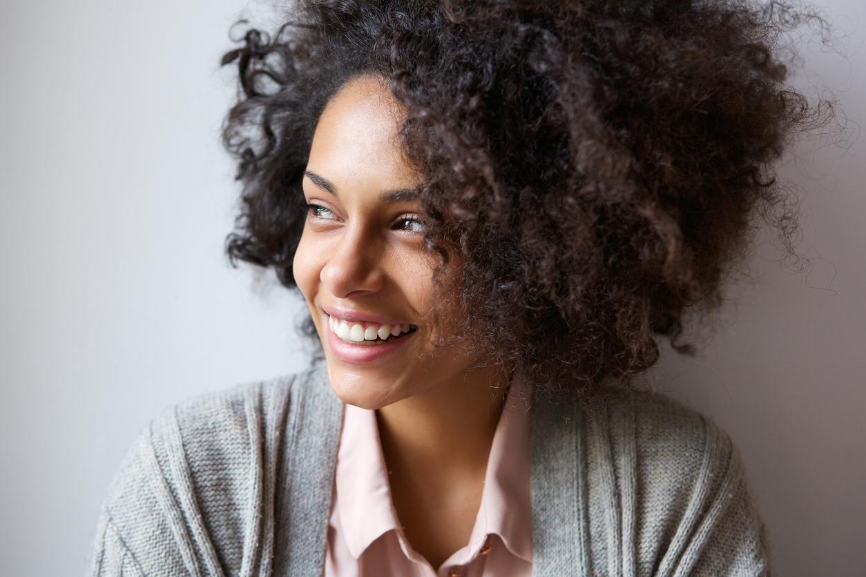 femme métisse noire naturelle cheveux afro sourire rire garder le moral