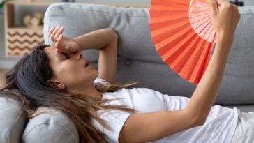 femme avoir trop chaud se rafraichir éventail été chaleur canapé