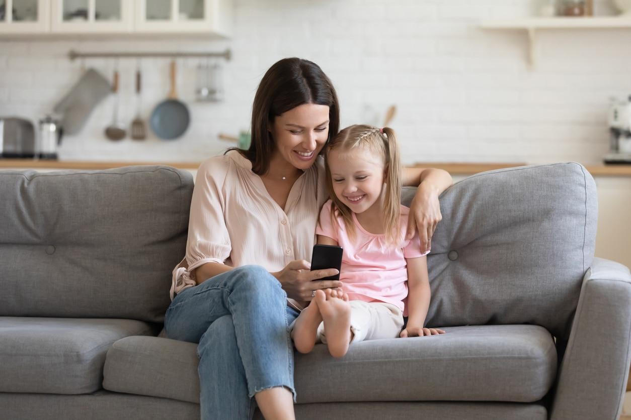 mère enfant fille canapé téléphone smartphone lumière bleue