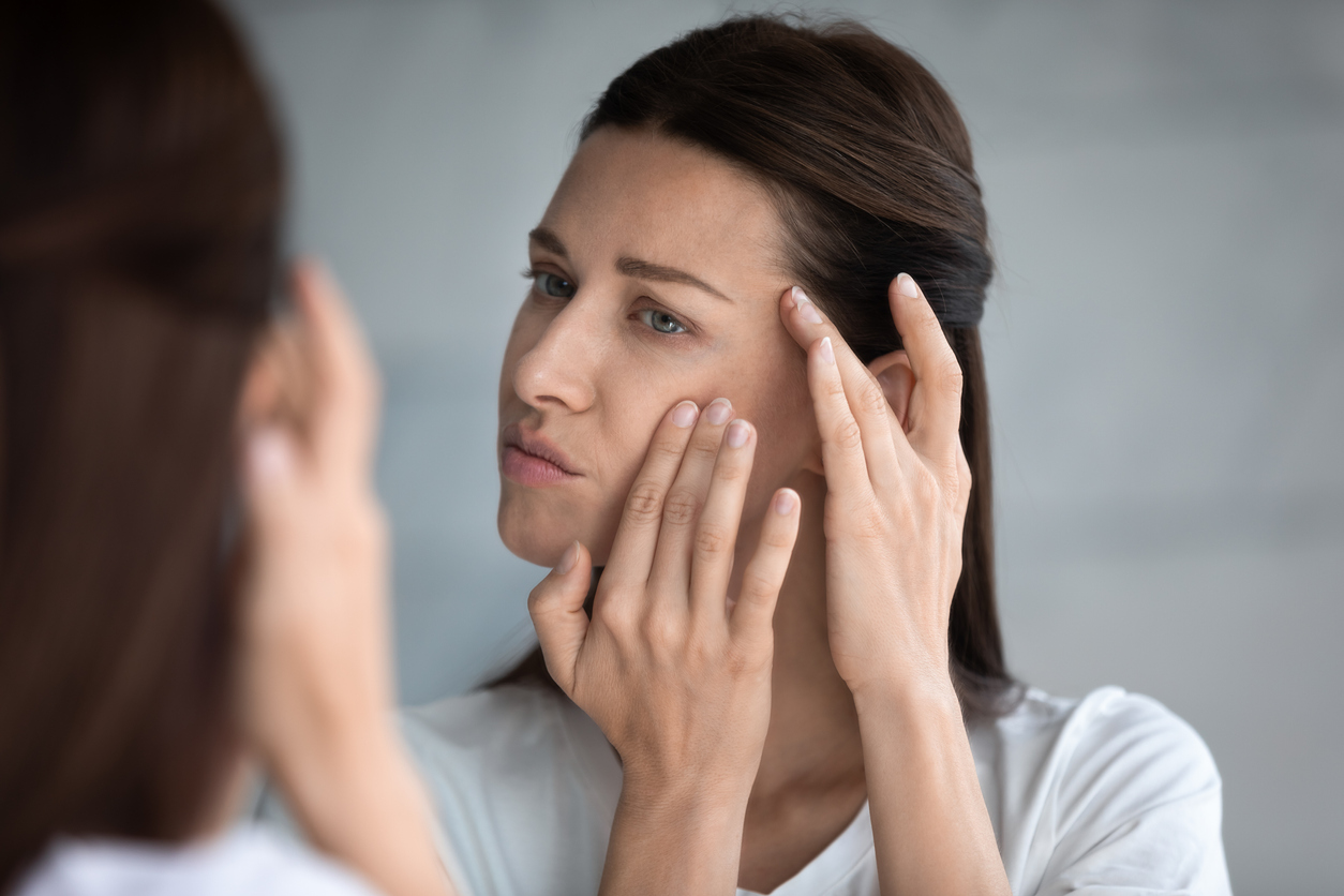 femme brune miroir rides peau visage bouton apparition ridules prévenir